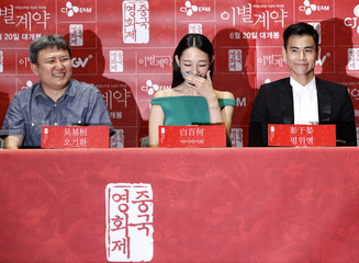 """Director Oh, cast members Bai and Peng react as they listen to reporter's question during news conference to promote their movie """"A Wedding Invitation"""", the closing film of the Chinese Film Festival, in Seoul"""