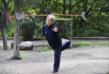 """A woman balances the """"Yue Ya Chan"""", a traditional Chinese pole weapon, on her head as she exercises in a park in Xi'an"""