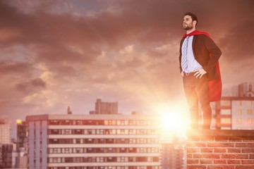 Composite image of businessman pretending to be super hero with