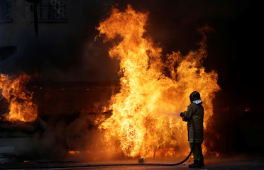 A firefighter tries to extinguish a fire of a bus burnt by anti-government demonstrators after a clash with riot policemen, during a protest against the Rio de Janeiro state government and a plan that will limit public spending, in Rio de Janeiro