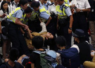 Police officers drag a protester away during a confrontation outside the Legislative Council in Hong Kong