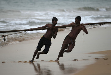 Two youths pull a fish net as they help a fisherman on a beach in Colombo