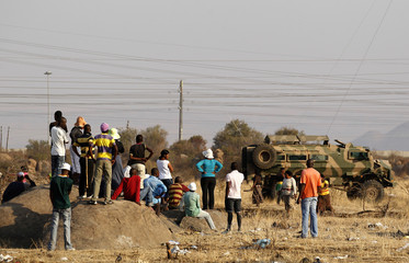 Locals look on as police patrol the area around where the shooting of striking miners occurred on Thursday outside a South African mine in Rustenburg