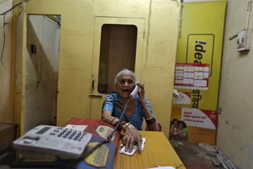 Shradeshshari Devi, 74, speaks on a phone at a local telephone booth in the old quarters of Delhi