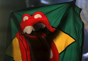 "A fan of British veteran rockers The Rolling Stones holds a flag during a concert on their ""Latin America Ole Tour"" in Rio de Janeiro"