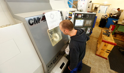 Employee operates a CNC machine at the factory of Maprox engineering company in Wetzikon