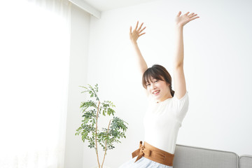 Young woman stretching her arms伸びをする若い女性