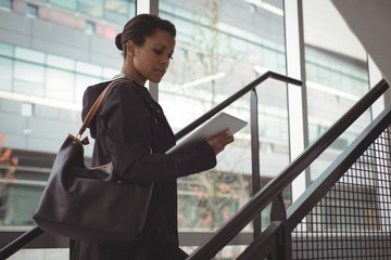 Side view of businesswoman looking at digital tablet