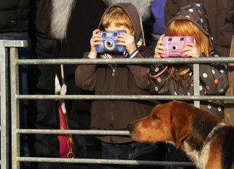 Young photographers take photographs of hounds as the New Forest Hunt gathers at at Boltons Bench for the annual Boxing Day hunt in Lyndhurst