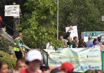 Demonstrators are seen outside site of Republican U.S. presidential candidate Romney's campaign stop at Tom's Ice Cream Bowl in Zanesville