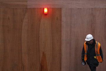 A worker walks past a construction site in London