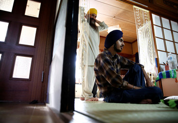 Gursewak Singh and his father Bharpoor Singh are seen in the living room of their house during an interview with Reuters in Matsudo