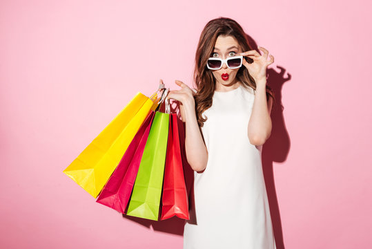 Shocked young brunette lady with shopping bags