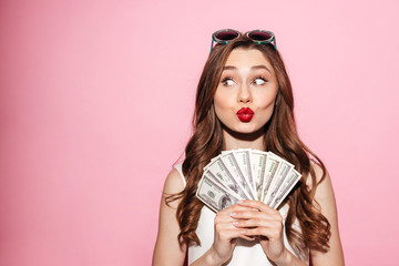 Funny young brunette lady holding money