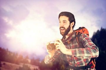 Composite image of happy hiker taking picture through camera
