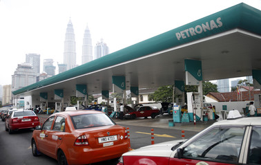 Motorists queue to fill up on natural gas at a Petronas station, with the company's headquarters at the landmark Petronas Twin Towers visible in the background, in Kuala Lumpur