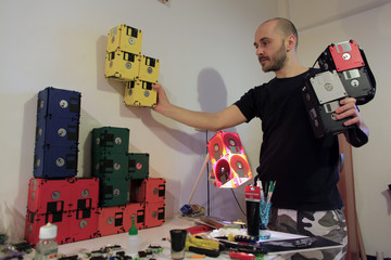 Romanian actor Alin Teglas arranges purses made from used floppy disks in his kitchen-workshop in Bucharest