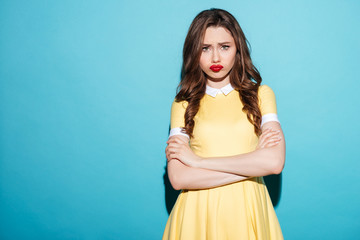 Cute upset girl in dress standing with arms folded