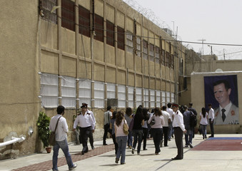 Journalists enter Branch Damascus Central Prison to attend the opening of an art exhibition by prisoners in Adra area