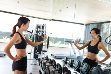 Young woman taking selfie in gym room