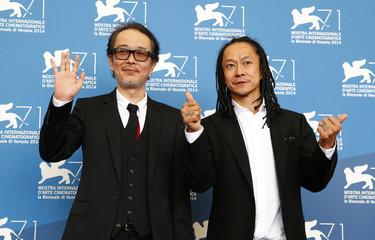 """Cast members Franky and Nakamura pose during the photo call for the movie """"Nobi"""" (Fires On The Plain) at the 71st Venice Film Festival"""