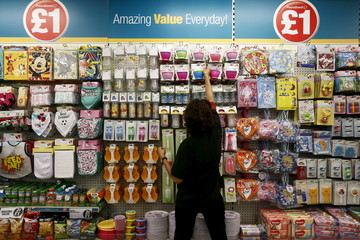 File photo of a Poundland employee checking products in a store in London