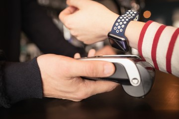 Woman paying through smartwatch using NFC technology