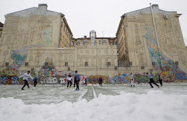 People play soccer in front of a mural creation called City in St. Petersburg