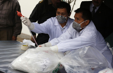 Anti-narcotics police chemists test cocaine from a bag before sending it for incineration in Lima
