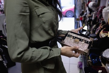 Mid section of woman holding glittery purse in jewelry section