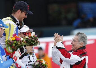 Austria's President Heinz Fischer applauds after presenting first placed Aksel Lund Svindal of Norway with a bouquet of flowers during the flower ceremony of the men's Downhill race at the World Alpine Skiing Championships in Schladming