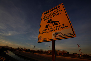 Sign warning immigrants to the dangers of swimming at the Rio Bravo, natural boundary with El Paso, U.S. (seen in the background), is pictured in Ciudad Juarez
