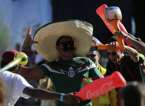 A soccer fan wearing a Mexican hat jokes with other fans during the 2014 World Cup soccer match between Brazil and Mexico at a FIFA event in Curitiba