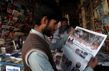 A man reads a newspaper's coverage of the attack on the Police Training College, at a newsstand in Quetta