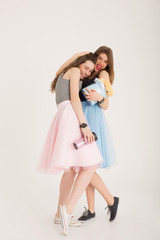 Happy best girlfriends with bouquet of roses in flower delivery present box and hot mug huging each other isolated. Smiling girls huging wearing pastel color skirts