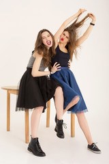 Rock and roll girls fooling around sitting on a wooden table isolated. Emotional best girlfriends rocking wearing skirts and dark lipstick. Vertical