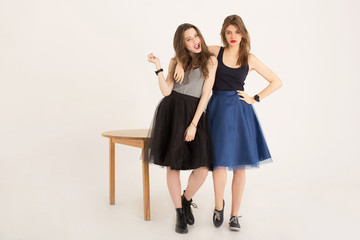 Rock and roll girls fooling around next to a wooden table isolated. Cheerful emotional best girlfriends rocking wearing skirts and dark lipstick