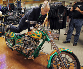 Former New York City Mayor and possible Republican presidential candidate Giuliani climbs off a motorcycle on display in Manchester