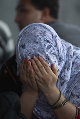 A detained ethinc Hazara woman covers her face at Pondok Dayung in Jakarta