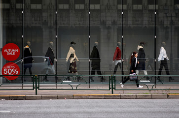 Woman runs past a fashion boutique in a shopping district in Tokyo
