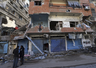 Free Syrian Army fighters stand in front of buildings damaged during fighting in Haresta neighborhood of Damascus