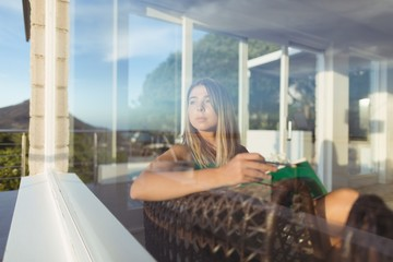 Thoughtful woman relaxing on chair and looking through window