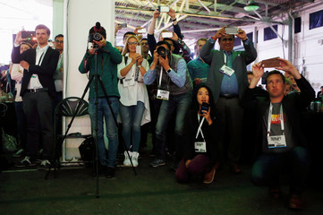 Attendees take pictures as Boston Dynamics' Spot robot walks on stage during 2016 TechCrunch Disrupt in San Francisco, California