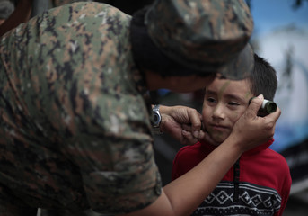 A member of Guatemala's army applies camouflage paint on a child during an event in Guatemala City