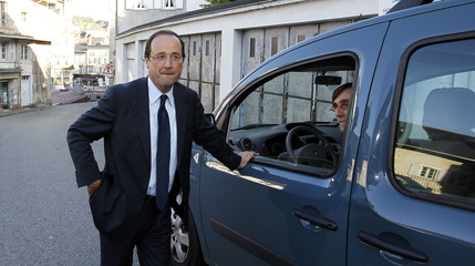 Francois Hollande, candidate in France?s Socialist Party run-off presidential primary election, speaks with a supporter as he arrives at a polling station in Laguenne