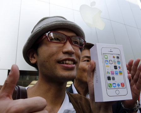 A man holds a box of Apple Inc's new iPhone 5S after waiting since September 10, outside an Apple Store at Tokyo's Ginza shopping district