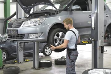 Mechaniker beim Scheibenwechsel in einer Autowerkstatt
