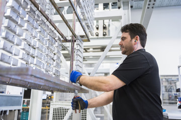 Man working in factory shop floor hanging products on rack
