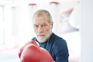 Portrait of serious senior man with earphones and boxing gloves in gym