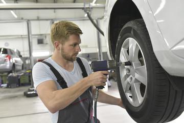 Reifenwechsel durch Monteur in einer Autowerkstatt